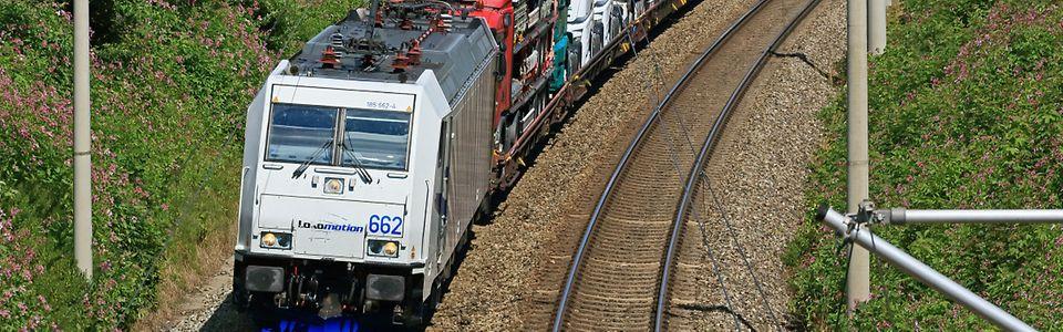 Eine Ellok der Baureihe 185 des EVU Lokomotion GmbH durchfährt mit einem Zug voller fabrikneuer Mercedes-Lkw zwischen Traunstei