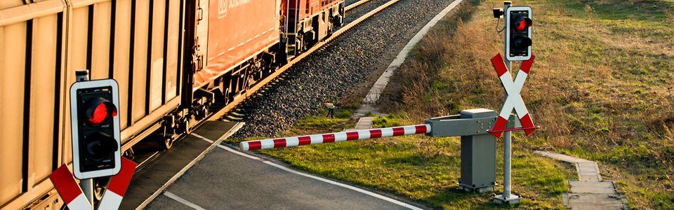 Bahnübergang mit Halbschranke und Lichtsignal